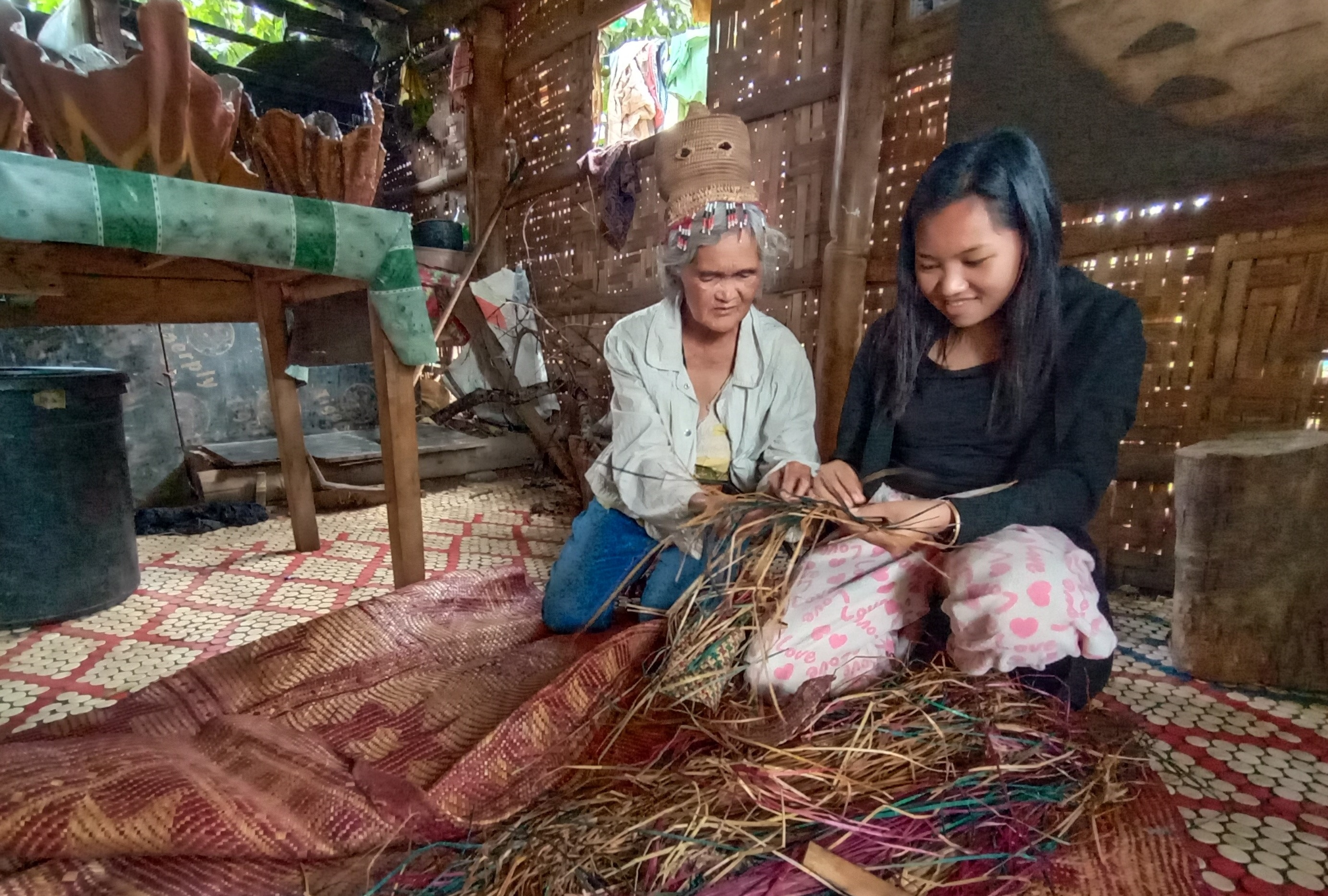 Nay Ipang mentors her child Dayan on mat weaving according to their culture's techniques and principles. She says weaving should be done only in the morning and in the late afternoon until evening. She believes that by noon grass is brittle.